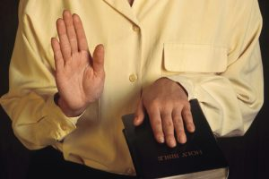 expert with hand on Bible