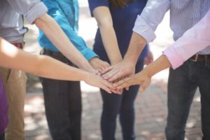 a group of people touching hands