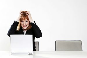 woman holding head in hands in front of computer