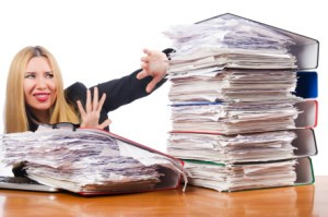 woman with pile of papers, writer's block