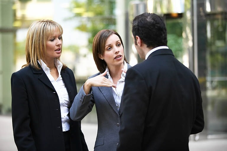 two women talking to a man
