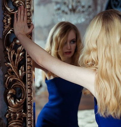 woman looking in mirror wondering if she is an imposter